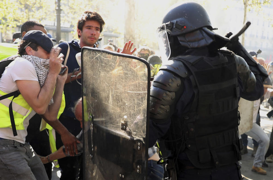 Police scuffle with protestors during a yellow vest demonstration in Paris, Saturday, April 20, 2019. French yellow vest protesters are marching anew to remind the government that rebuilding the fire-ravaged Notre Dame Cathedral isn't the only problem the nation needs to solve. (AP Photo/Francisco Seco)