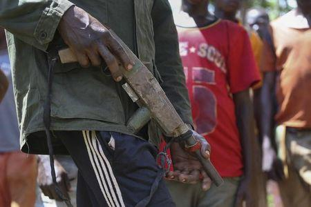 An anti-Balaka soldier holds a handmade gun as former child soldiers wait to be released in Bambari