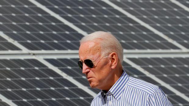 Joe Biden walks past solar panels while touring the Plymouth Area Renewable Energy Initiative in Plymouth, New Hampshire, U.S., June 4, 2019.