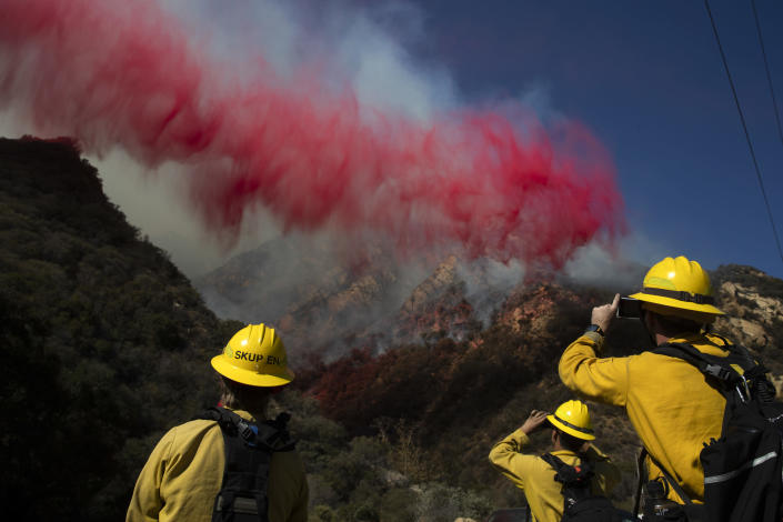 FILE - In this Nov. 11, 2018 file photo firefighters take pictures of fire retardant dropped on a burning hillside in Malibu, Calif. A group of U.S. senators from around the American West sent a letter to President Trump warning that firefighting academies that provide required annual training for thousands of front-line fire crews are canceling classes because their federally employed instructors are on furlough. (AP Photo/Jae C. Hong)