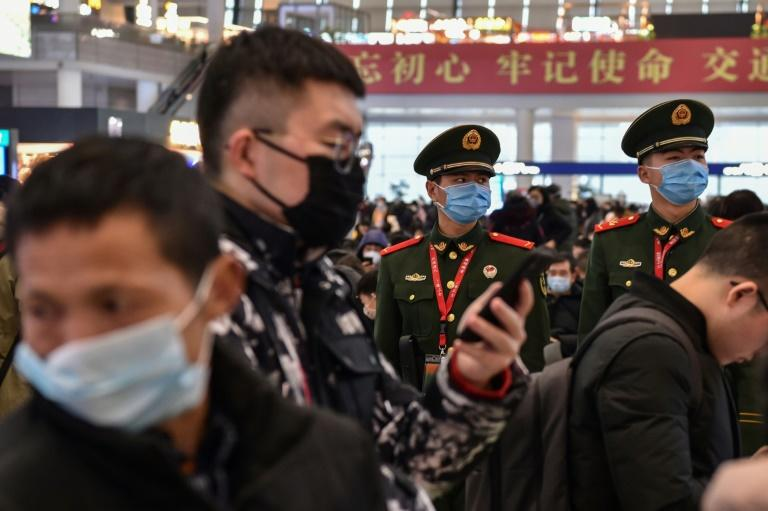 Chinese paramilitary police wearing masks stand guard at a Shanghai train station as the country faces a virus crisis at the start of the Lunar New Year holiday (AFP Photo/HECTOR RETAMAL)