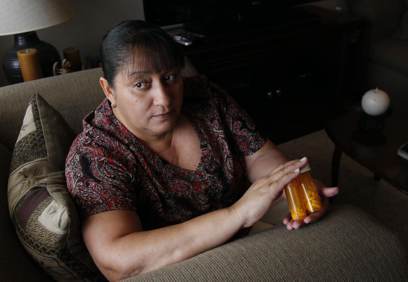 In a Thursday, July 26, 2012 photo, Sandra Pico, 52,  holds medications she takes, at her home in North Miami Beach, Fla. Pico makes about $15,000 a year working about 20 hours a week as a home health aide, a bit too much to qualify for Medicaid, but not enough that she can afford private insurance. She thought she'd be getting health insurance after the Supreme Court upheld the health care law. Then she learned her own governor won't agree to expand Medicaid under the law which would have given her coverage. (AP Photo/Lynne Sladky)