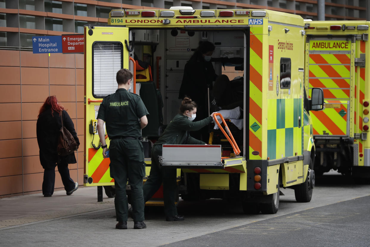 Medics prepare to take a patient out from the back of an ambulance after arriving outside the Royal London Hospital in east London, Thursday, Feb. 4, 2021, during England's third national lockdown since the coronavirus outbreak began. The U.K. is under an indefinite national lockdown to curb the spread of the new variant, with nonessential shops, gyms and hairdressers closed, most people working from home and schools largely offering remote learning. (AP Photo/Matt Dunham)