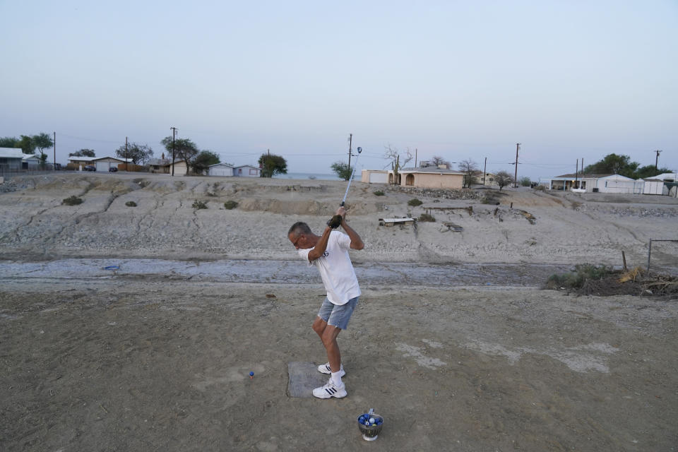 Greg Shank hits golf balls onto a dried up boating dock near his home in Salton City, Calif., Wednesday, July 14, 2021. Shank used to sail a boat on the canals near his property, which have since dried up. Increasing demand for electric vehicles has shifted investments into high gear to extract lithium, critical to rechargeable batteries, from geothermal wastewater around the rapidly shrinking body of water. But decades of economic stagnation and environmental ruin have left some nearby residents indifferent or wary. (AP Photo/Marcio Jose Sanchez)