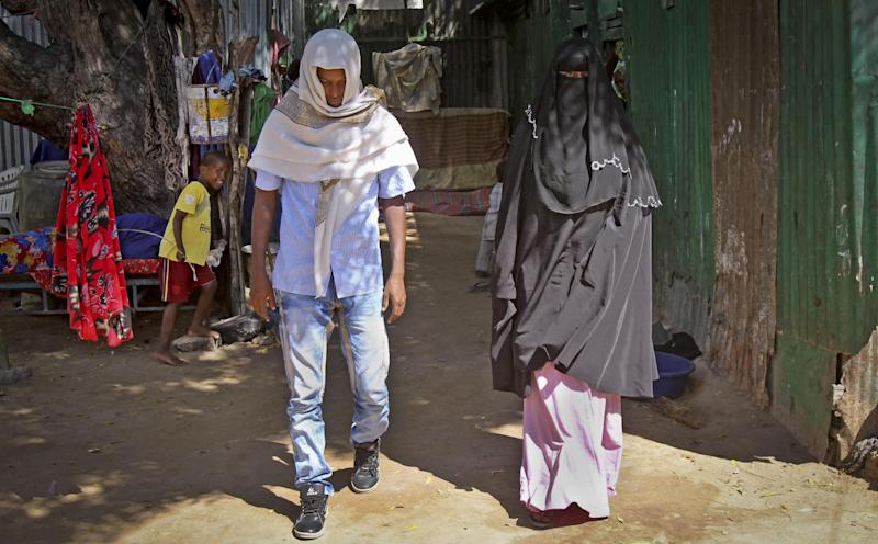 In this photo taken Wednesday, March 13, 2013, Abdi Ali, 25, and his girlfriend Anisa, 23, walk out after being married by an Islamic cleric who marries eloping couples, in Walaweyn, Somalia. Since the Islamic extremist rebels of al-Shabab have been pushed out of almost all of Somalia's cities and towns, life has begun to return to normal - including elopements which al-Shabab under its strict interpretation of Islamic Shariah law had declared illegal and punishable by whipping or even death by stoning. (AP Photo/Farah Abdi Warsameh)