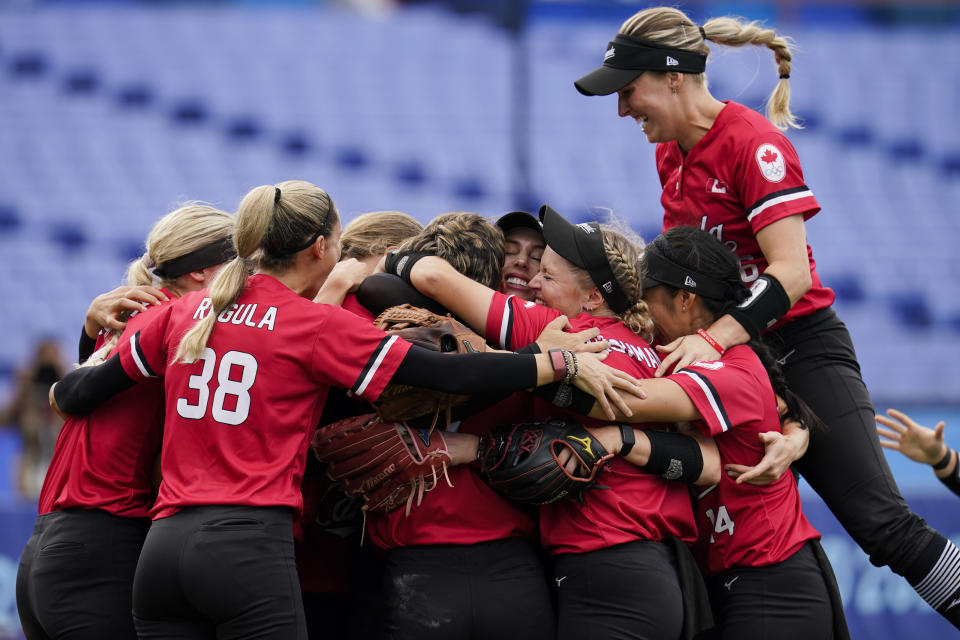 Members of team Canada celebrate after defeating Mexico in a softball game at the 2020 Summer Olympics, Tuesday, July 27, 2021, in Yokohama, Japan (AP Photo/Sue Ogrocki)