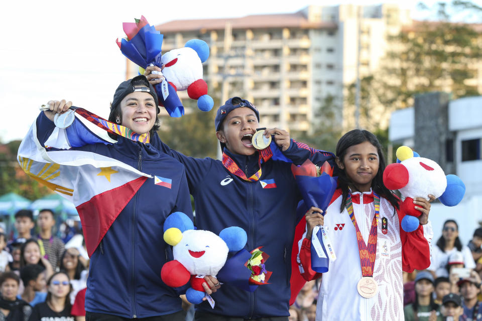 Gold medalist Philippines' Margielyn Didal, center, poses with silver medalist Philippines' Christiana Means, left, and bronze medalist Indonesia's Kyandra Susanto during the awarding ceremony of the street event finals of skateboarding at the 30th South East Asian Games in Tagaytay City, Cavite Province, Philippines, on Saturday, December 7, 2019. (AP Photo/Jijo de Guzman)