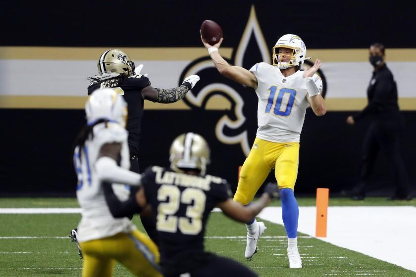 Los Angeles Chargers quarterback Justin Herbert (10) throws the ball in front of New Orleans Saints outside linebacker Demario Davis (56) during an NFL football game, Monday, Oct. 12, 2020, in New Orleans. (AP Photo/Tyler Kaufman)