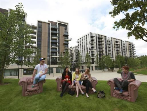 Students who were asked to test facilities for the night sit in Victory Park in the Olympic Village built for the London 2012 Olympic Games in Stratford, east London June 29, 2012.
