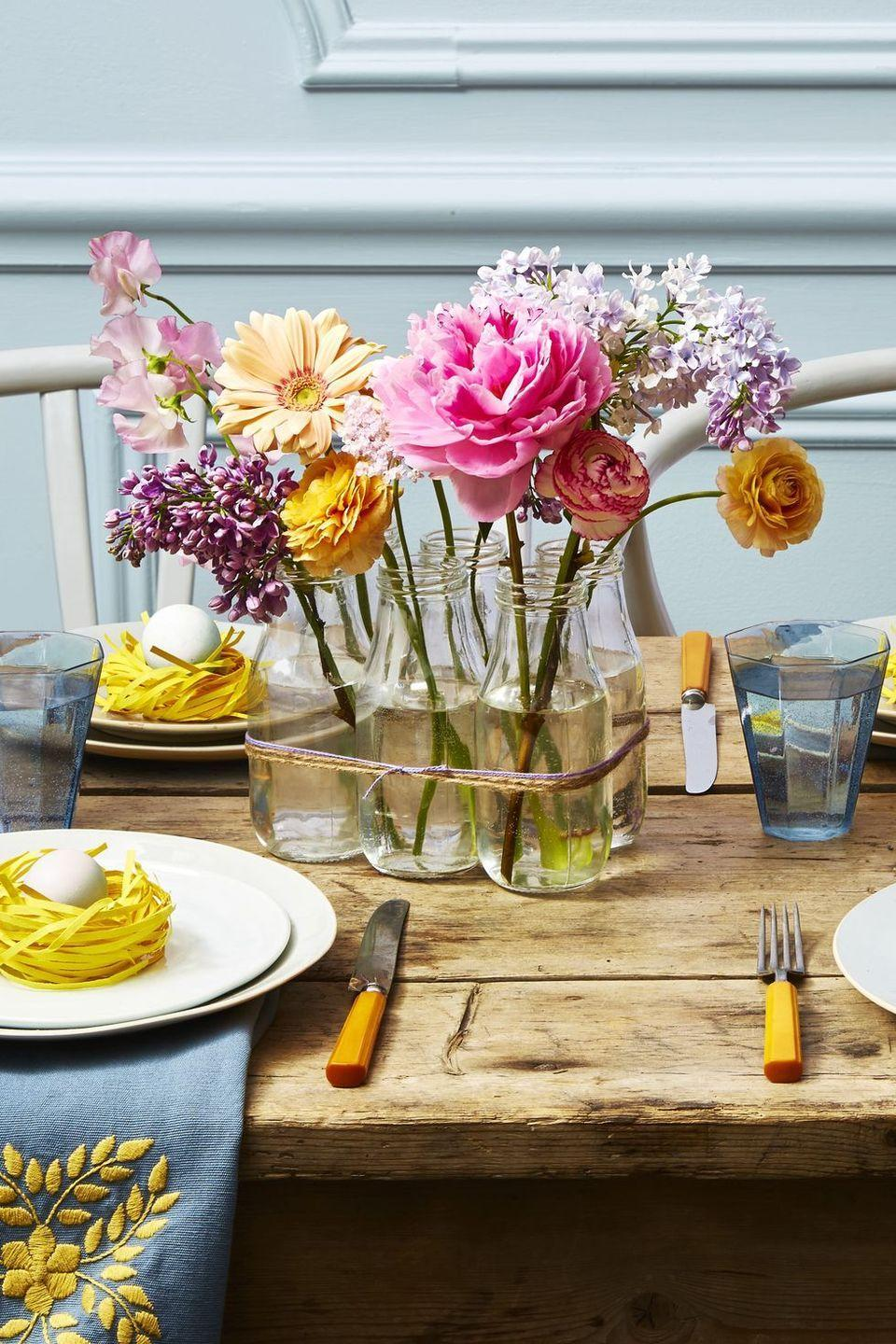"""<p>For an unexpected look, string together a bunch of empty milk jars, and fill with a mixture of small and large blooms.</p><p><a class=""""link rapid-noclick-resp"""" href=""""https://www.amazon.com/Natural-100PCS-Retangle-Crafts-Blisstime/dp/B01LZBECKU/?tag=syn-yahoo-20&ascsubtag=%5Bartid%7C10055.g.1906%5Bsrc%7Cyahoo-us"""" rel=""""nofollow noopener"""" target=""""_blank"""" data-ylk=""""slk:SHOP TWINE"""">SHOP TWINE</a></p><p><strong>RELATED:</strong> <a href=""""https://www.goodhousekeeping.com/holidays/easter-ideas/g2217/easter-decorations/"""" rel=""""nofollow noopener"""" target=""""_blank"""" data-ylk=""""slk:Easter Decorations You Can Easily DIY"""" class=""""link rapid-noclick-resp"""">Easter Decorations You Can Easily DIY </a></p>"""