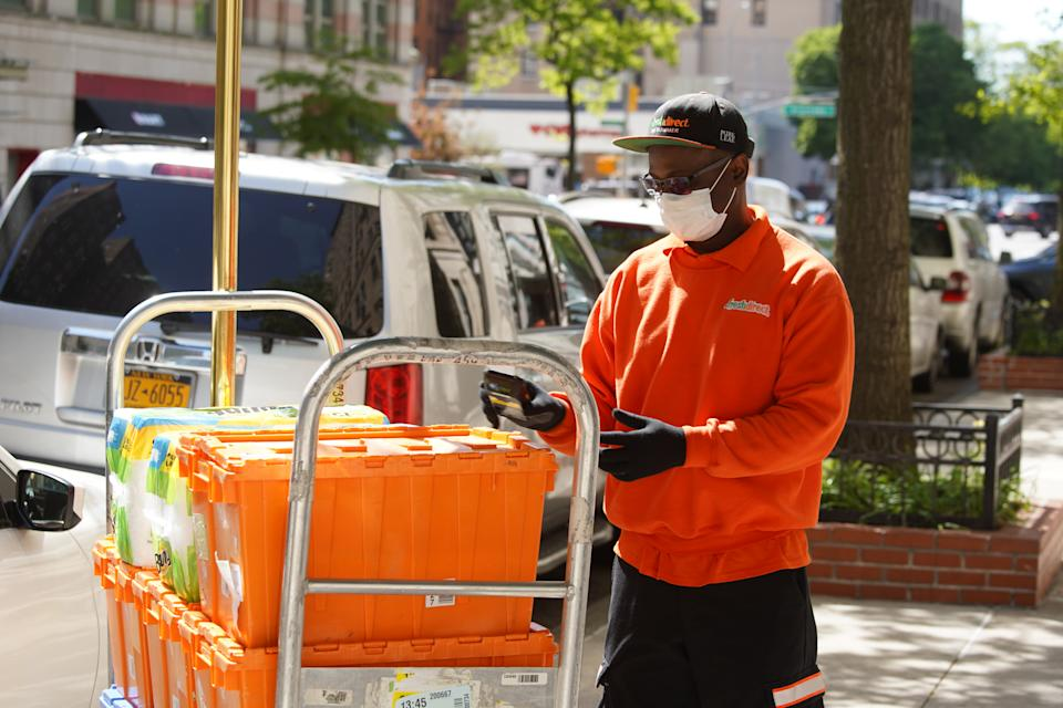 NEW YORK, NEW YORK - MAY 21:  A Fresh Direct worker in protective face mask and gloves handles deliveries on May 21, 2020 in New York City. COVID-19 has spread to most countries around the world, claiming over 332,000 lives with infections of over 5.1 million people. (Photo by Rob Kim/Getty Images)