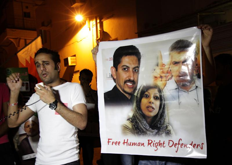 In this photo taken Aug. 12, 2012, human rights activist Sayyed Yousif al-Muhafdha, left, speaks to protesters during a march in Bilad al-Qadeem, Bahrain, calling for freedom for jailed rights activists seen on the poster at right, Abdul Hadi al-Khawaja, upper left, Nabeel Rajab, upper right, and Zainab al-Khawaja lower center. Opposition activists said Wednesday that al-Muhaddha was arrested at a police checkpoint in A'ali Village. (AP Photo/Hasan Jamali)