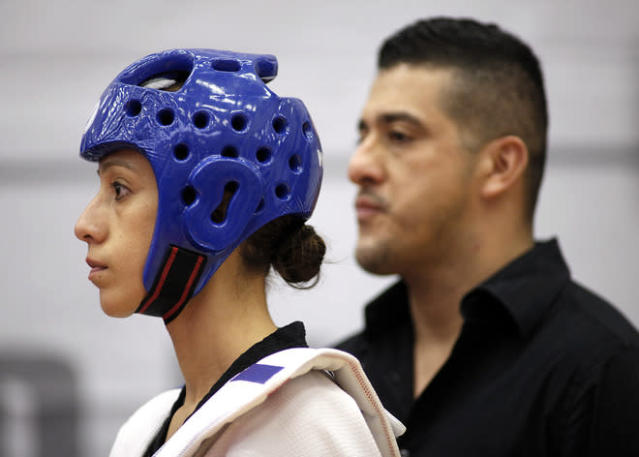 COLORADO SPRINGS, CO - MARCH 10: Diana Lopez, left, gets ready to square off against Danielle Holmquist as her older brother and coach Jean Lopez stands in the background during the 2012 Taekwondo Olympic Trials at the U.S. Olympic Training Center on March 10, 2012 in Colorado Springs, Colorado. Lopez won the match 3-1. (Photo by Marc Piscotty/Getty Images)