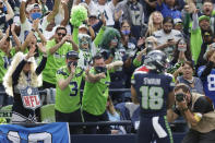 Seattle Seahawks fans react after wide receiver Freddie Swain (18) scored a touchdown against the Tennessee Titans during the second half of an NFL football game, Sunday, Sept. 19, 2021, in Seattle. (AP Photo/John Froschauer)