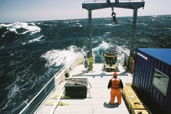 In stormy waters, scientists prepare to drop an ocean-collecting device into the water.