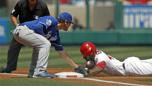 Los Angeles Angels' Howard Kendrick is safe at third ahead of the tag of Kansas City Royals third baseman Mark Trumbo, starting from first on a wild pitch by Jonathan Sanchez in the second inning of a baseball game at Anaheim, Calif., Sunday, April 8, 2012. (AP Photo/Reed Saxon)