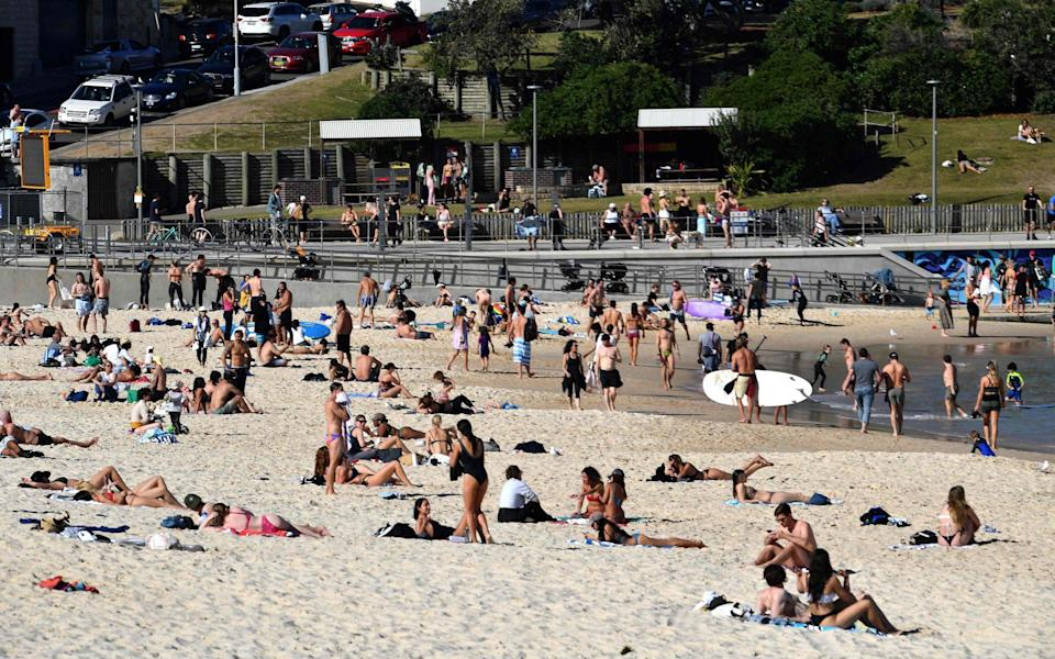 People relaxed at Bondi Beach in Sydney on Wednesday as authorities announced that millions of residents will spend another month in lockdown - SAEED KHAN/AFP