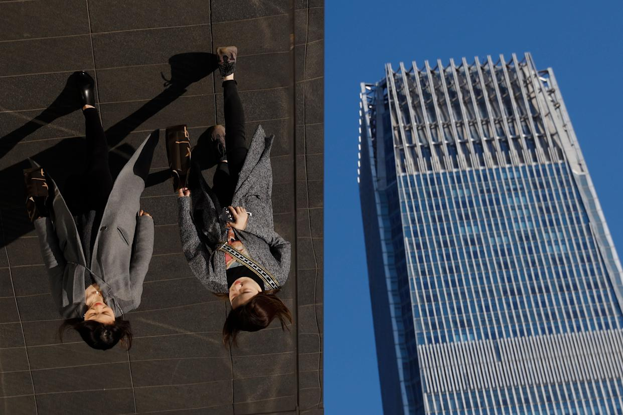 In this March 6, 2019, photo, women are reflected on silver panels of the French luxury brand Louis Vuitton flagship store at the Central Business District in Beijing. China will bar government authorities from demanding overseas companies hand over technology secrets in exchange for market share, a top economic official said Wednesday, addressing a key complaint at the heart of the current China-U.S. trade dispute. (AP Photo/Andy Wong, File)