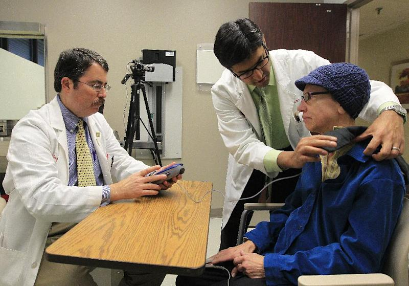 Dr. Doug Scharre, left, and Dr. Punit Agrawal, center, prepare Kathleen Sanford's deep brain stimulation device for monitoring Monday, Dec. 17, 2012, in Columbus, Ohio. Sanford is an Alzheimer's patient that has a deep brain stimulation implant as part of a study at Ohio State University. In small experiments, scientists are implanting pacemaker-like devices deep in the brains of some people with early-stage Alzheimer's in hopes of slowing the disease's damage. The tiny wires send mild jolts of electricity to stimulate the brain. (AP Photo/Jay LaPrete)
