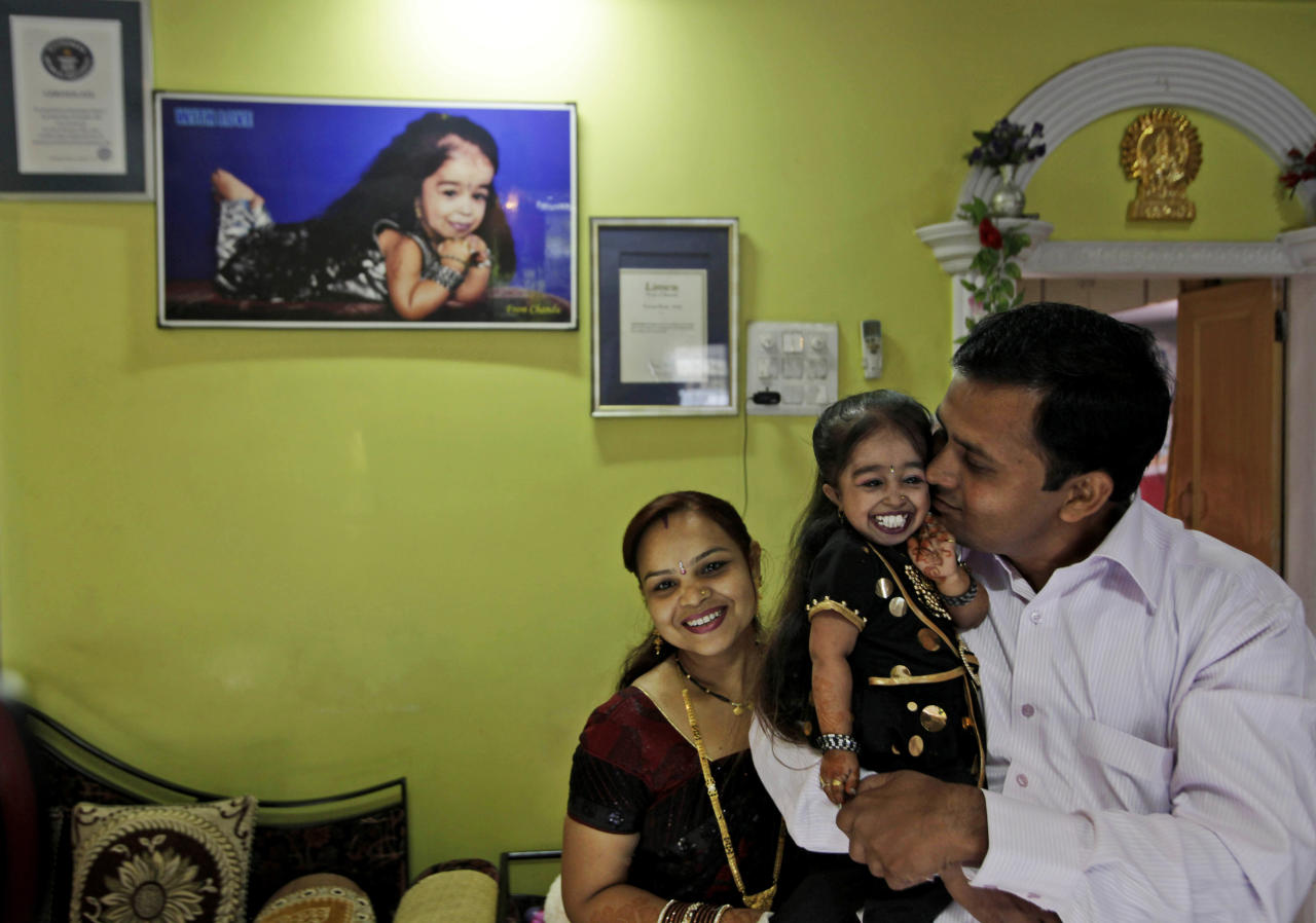 Unidentified relatives congratulate Jyoti Amge, 18, who stands at 61.95 centimeters (2 feet) at her residence before a press conference with Guinness World Records in Nagpur, India, Friday, Dec. 16, 2011. Officials from Guinness were expected to measure Amge later Friday and declare her the World's Shortest Woman. (AP Photo/Manish Swarup)