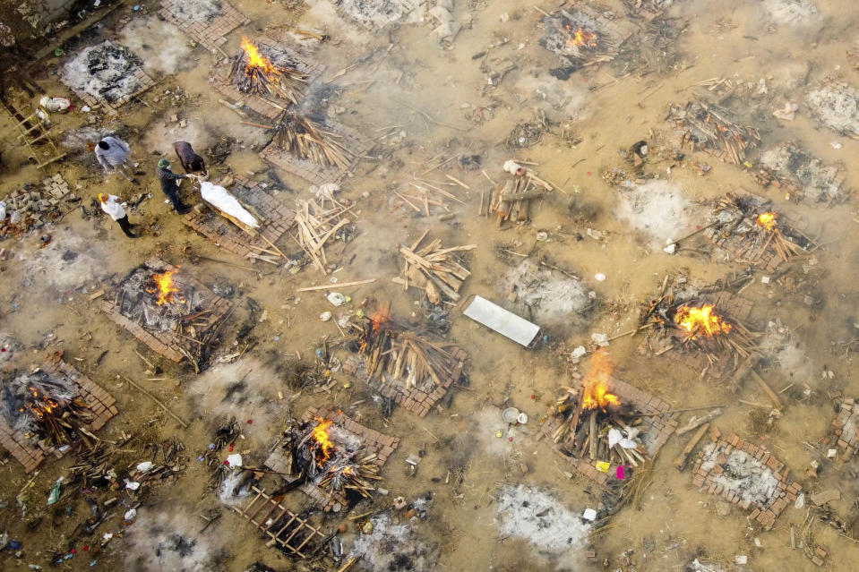 TOPSHOT - In this aerial picture taken on April 26, 2021, relatives and friends of a victim who died of the Covid-19 coronavirus gather to cremate the body at a cremation ground in New Delhi. (Photo by Jewel SAMAD / AFP) (Photo by JEWEL SAMAD/AFP via Getty Images)