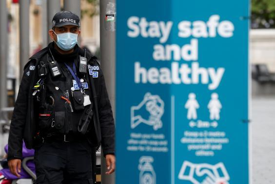 A police officer wearing a protective mask patrols the streets of Leicester following the reintroduction of lockdown (Reuters)