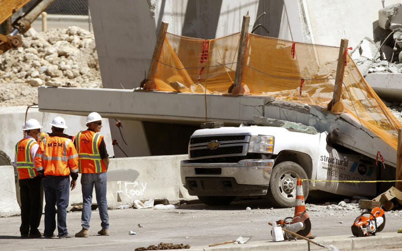 <p> Workers stand next to a section of a collapsed pedestrian bridge, Friday, March 16, 2018 near Florida International University in the Miami area. The new pedestrian bridge that was under construction collapsed onto a busy Miami highway Thursday afternoon, crushing vehicles beneath massive slabs of concrete and steel, killing and injuring several people, authorities said. (AP Photo/Wilfredo Lee) </p>