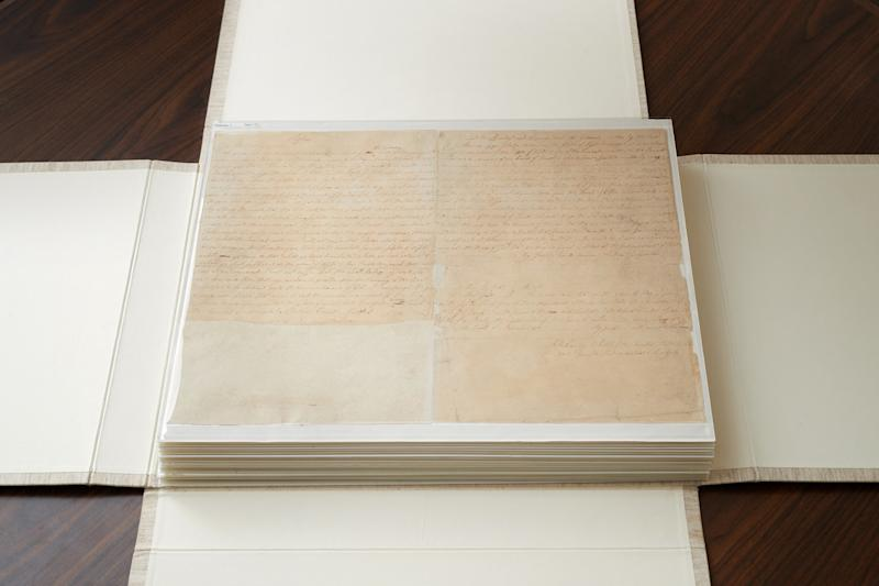 These are the first couple of pages of the printer's manuscript of the Book of Mormon. It is enclosed by folding the casing and then by sliding it into an additional case. (Intellectual Reserve Inc)