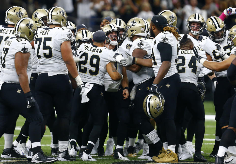 New Orleans Saints players surround quarterback Drew Brees after Brees broke the NFL all-time passing yardage record. (AP)