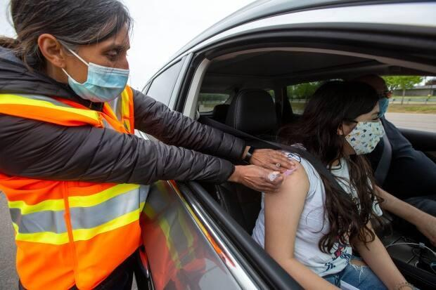 A passenger receives a COVID-19 vaccine from Dr. Rupa Patel at a drive-thru clinic at Richardson Stadium in Kingston, Ont., on May 28, 2021. (Lars Hagberg/Canadian Press - image credit)