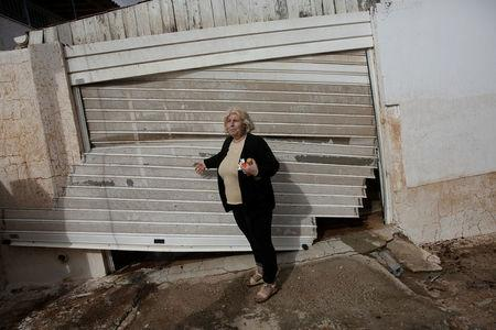 Local Konstantina Louka stands next to her destroyed garage entrance following a heavy rainfall in the town of Mandra, Greece, November 15, 2017. REUTERS/Alkis Konstantinidis
