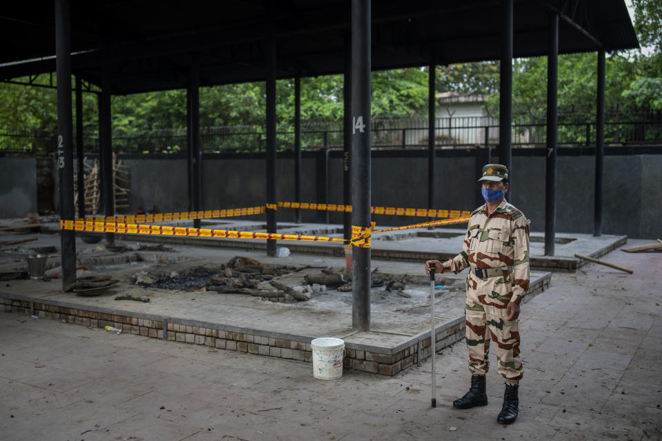 An Indian paramilitary soldier stands guard near a pyre inside a crematorium where a 9-year-old girl from the lowest rung of India's caste system was cremated, earlier this week, in New Delhi, India, Thursday, Aug. 5, 2021. Angry villagers held a protest saying the girl was raped and killed. (AP Photo/Altaf Qadri)