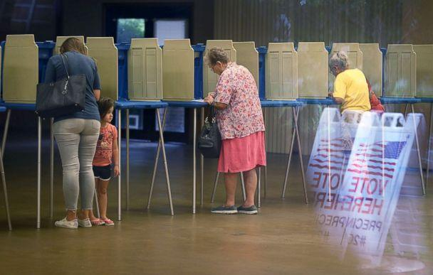 PHOTO: Fionna Beazzo stands with her mother Erin Beazzo as she fills out her primary day voting ballot next to Beverly Putzke at a polling station, Aug. 28, 2018, in St. Augustine, Fla. (Joe Raedle/Getty Images)