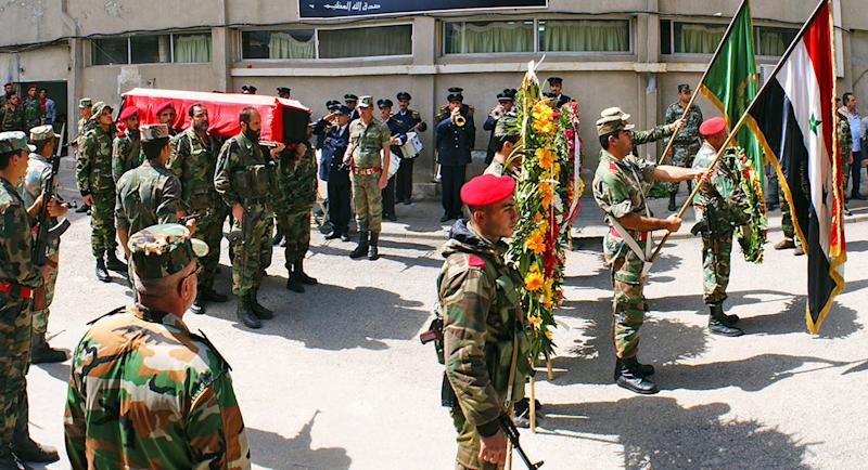 In this Monday, March 24, 2014 photo released by the Syrian official news agency SANA, Syrian soldiers carry the coffin of the commander of the pro-government National Defense Forces Hilal Assad, during his funeral at a hospital in Latakia province, Syria. State TV reported late Sunday that Hilal Assad was killed in the fighting against opposition fighters in Kassab. The commander was a member of Syrian President Bashar Assad's family but the TV did not say if they were close relatives. (AP Photo/SANA)
