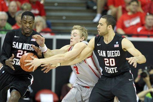 San Diego State's Jamaal Franklin, left, and JJ O'Brien, right, attempt to take the ball from New Mexico's Hugh Greenwood during the first half of a Mountain West Conference tournament NCAA college basketball game on Friday, March 15, 2013, in Las Vegas. (AP Photo/Isaac Brekken)