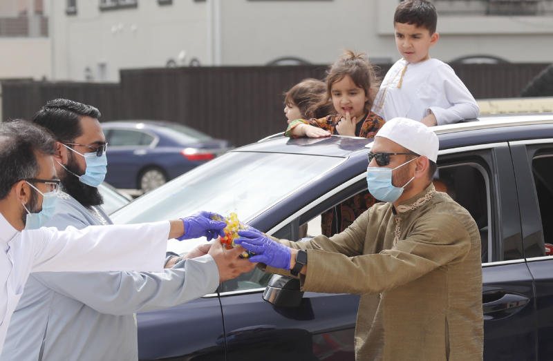 Children look on from a sunroof as organizers prepared to give them candy during an Eid al-Fitr drive through celebration outside a closed mosque in Plano, Texas, Sunday, May 24, 2020. Many Muslims in America are navigating balancing religious and social rituals with concerns over the virus as they look for ways to capture the Eid spirit this weekend. (AP Photo/LM Otero)