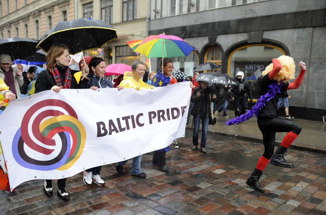 Participants in a gay pride parade march braving heavy rain in a street in Riga, Latvia, Saturday, June 2, 2012. Several hundred activists from the Baltic states and neighboring countries braved rain and hail to participate in an annual parade in defense of gay and lesbian rights in Latvia. (AP Photo/Roman Koksarov)