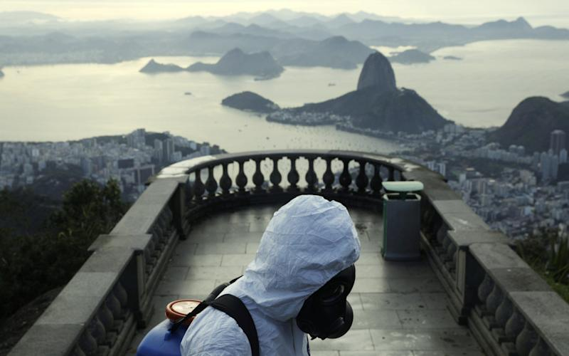 A Military member works on disinfection of the Christ the Redeemer statue, with the Sugar Loaf mountain on background ahead of its re-opening amid the coronavirus disease (COVID-19) outbreak, in Rio de Janeiro, Brazil - Ricardo Moraes/Reuters