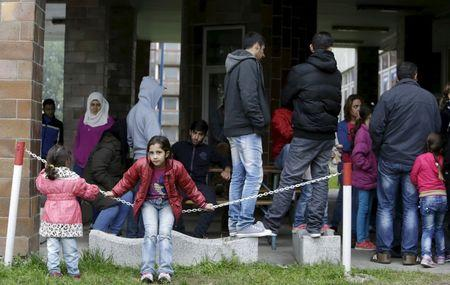 Syrian migrants, who said they were pressured by Austria to leave the country for Slovakia, gather in front of a building acting as a temporary refugee camp in Gabcikovo