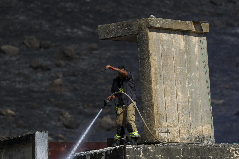 An Israeli firefighter works to extinguish a fire caused by rocket fired from Lebanon into Israeli territory near the northern Israeli town of Kiryat Shmona, Wednesday, Aug. 4, 2021. Three rockets were fired from Lebanon into Israeli territory Wednesday and the army fired back, Israel's military said. There was no immediate information on damages or casualties. (AP Photo/Ariel Schalit)