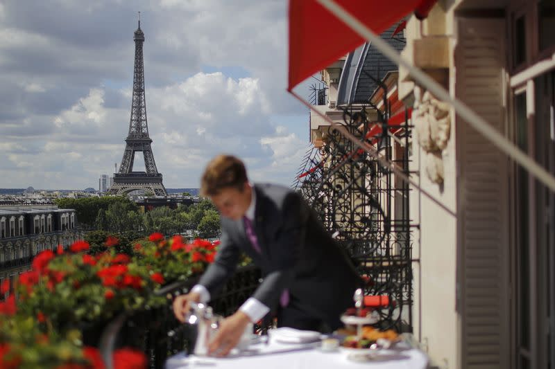 An employee prepares breakfast in front of the Eiffel tower at the Parisian luxury hotel Le Plaza Athenee