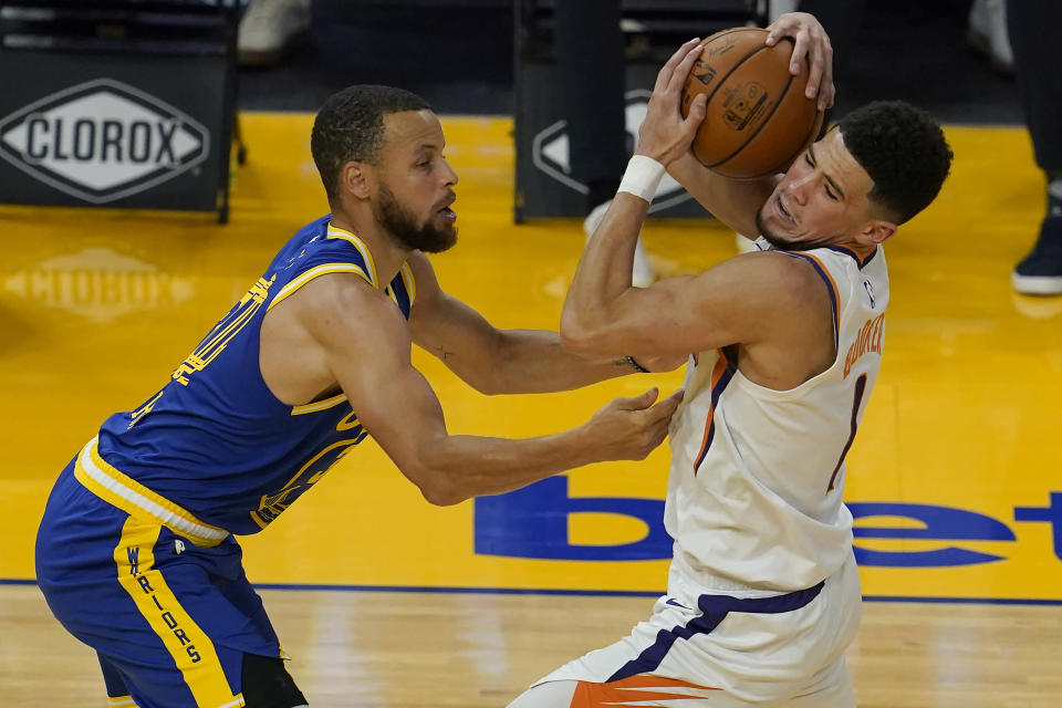 Phoenix Suns guard Devin Booker, right, is defended by Golden State Warriors guard Stephen Curry during the first half of an NBA basketball game in San Francisco, Tuesday, May 11, 2021. (AP Photo/Jeff Chiu)