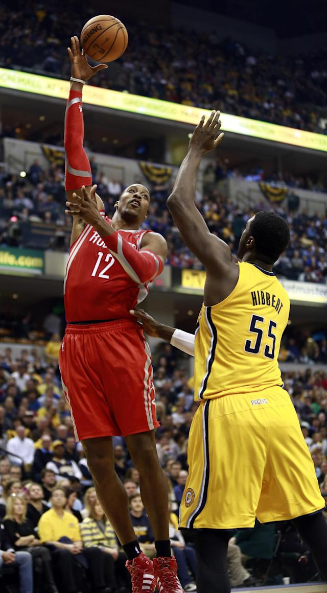 Houston Rockets center Dwight Howard (12) shoots over Indiana Pacers center Roy Hibbert (55) in the first half of an NBA basketball game in Indianapolis, Friday, Dec. 20, 2013. (AP Photo/R Brent Smith)