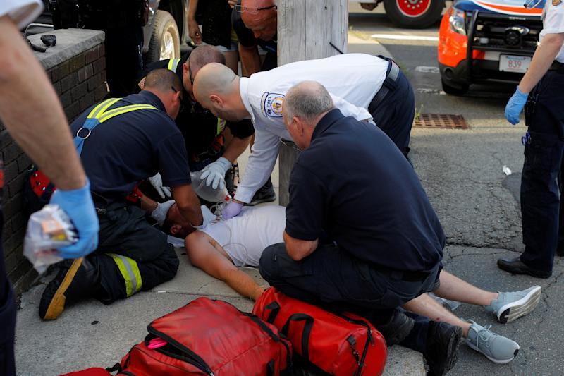 Paramedics and firefighters treat a 32-year-old man who was found unresponsive on a sidewalk after overdosing on opioids in Everett, Massachusetts, on Aug. 23, 2017.