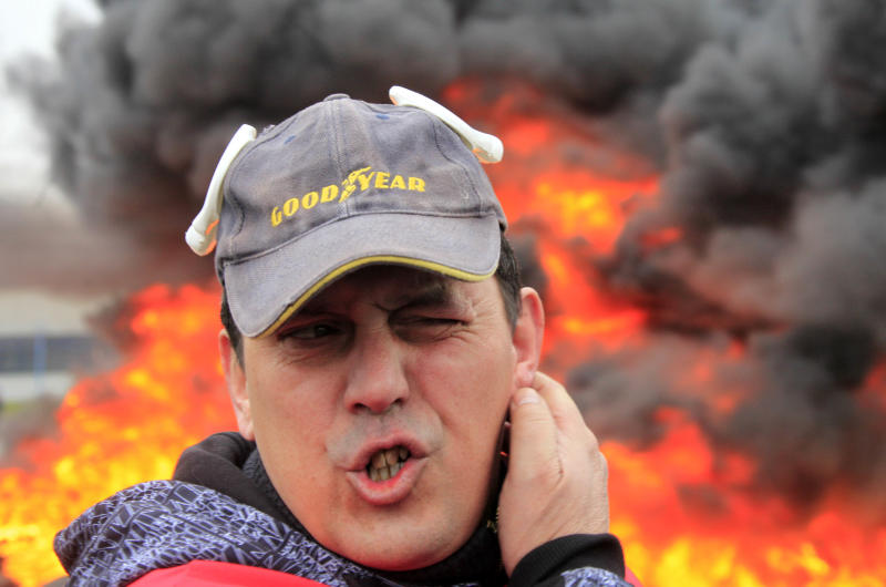 A Goodyear employee stands near burning tires, outside the Goodyear tire company, in Amiens, northern France, Tuesday Feb. 26, 2013. Workers at a dying French tyre factory who've become the butt of American jokes are staging a day of last-ditch protests to try to save their jobs. The protests in the northern city of Amiens come after efforts to find a new buyer for the struggling plant have fizzled. An American executive who considered buying it sent a letter last week to the French government saying that France's economic model is too worker-friendly and discourages investment. (AP Photo/Michel Spingler)