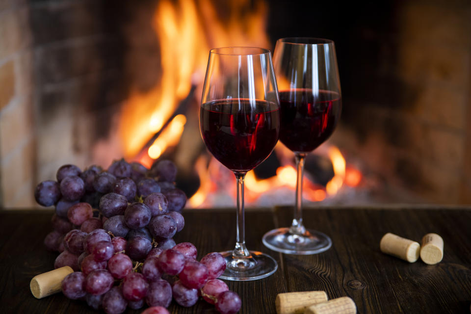 Two glasses of red wine with corks and grapes near the fireplace
