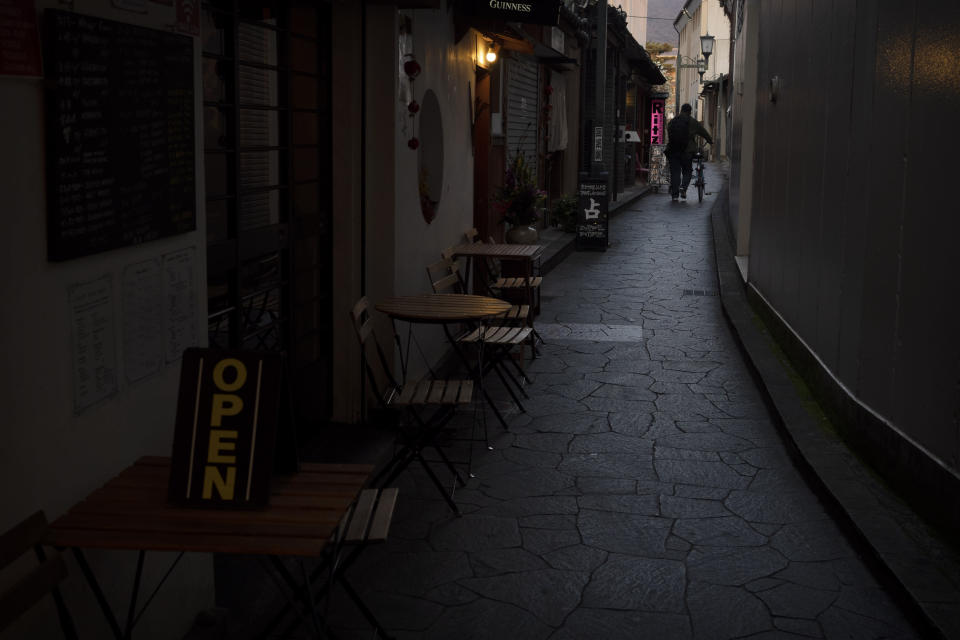 A man walks with his bike through a narrow alley lined with restaurants in Nara, Japan, Tuesday, March 17, 2020. (AP Photo/Jae C. Hong)