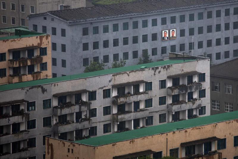Portraits of the late North Korean leaders Kim Il Sung, left, and Kim Jong Il hang on the outside of a building in central Pyongyang, North Korea, on Saturday, May 18, 2013. (AP Photo/David Guttenfelder)