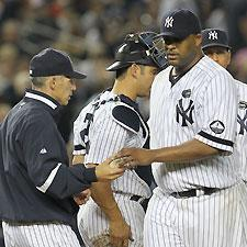A horrible sixth inning resulted in CC Sabathia (right) handing the ball over to Yankees manager Joe Girardi