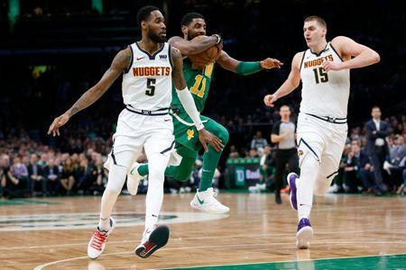 Mar 18, 2019; Boston, MA, USA; Boston Celtics guard Kyrie Irving (11) drives between Denver Nuggets guard Will Barton (5) and center Nikola Jokic (15) during the second half at TD Garden. Mandatory Credit: Greg M. Cooper-USA TODAY Sports